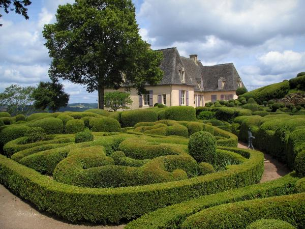 Marqueyssac gardens - Castle, hand-clipped box trees and clouds in the sky, in the Dordogne valley, in Périgord