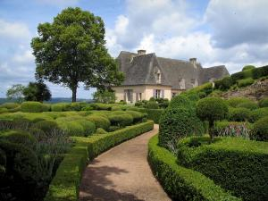 Marqueyssac gardens - Path and hand-clipped box trees, tree, castle and clouds in the sky, in the Dordogne valley, in Périgord
