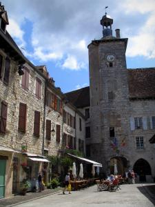 Martel - Bell tower of the Raymondie mansion, stone houses and restaurant terrace of the Consuls square, in the Quercy