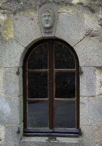 Masgot - Facade of a house with window topped by a sculpture