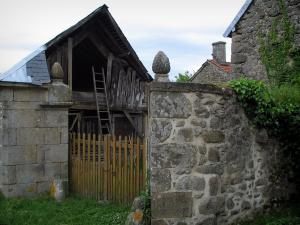 Masgot - Barn with a wooden ladder and stone houses of the village