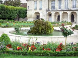Meaux - Pond with a rock and flowerbeds in the Bossuet garden (French-style formal garden of the former bishop's palace) and facade of the former Episcopal palace in the background