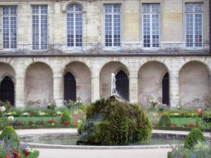 Meaux - Facade of the former bishop's palace and Bossuet garden (French-style formal garden of the former bishop's palace), rock of the pond and flowerbeds