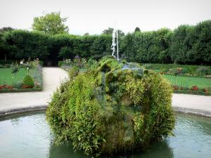 Meaux - Bossuet garden (French-style formal garden of the former bishop's palace): rock of the pond, flowerbeds, and trees