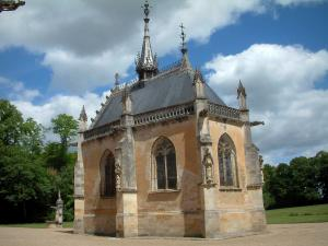 Meillant castle - Chapel, park with trees and clouds in the blue sky