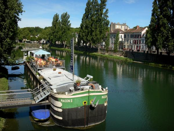 Melun - River Seine, moored barge, restaurant terrace, banks of the River Seine, facades of the city and trees along the water