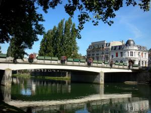Melun - Flower-covered bridge spanning the River Seine, facades of the city and trees along the water