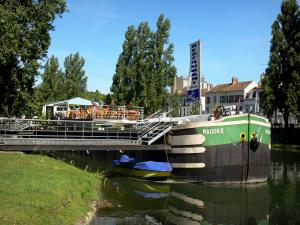 Melun - Banks of River Seine: moored barge with a terrace restaurant, River Seine, facades of the town and trees