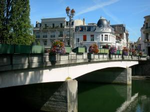 Melun - Flower-covered bridge spanning the River Seine, lamppost and facades of the town