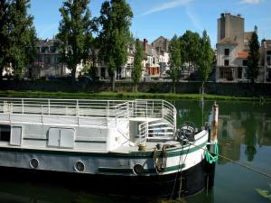 Melun - Banks of River Seine: moored barge, river, facades of the town and trees along water