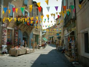 Ménerbes - Street in the village with houses, shops and small colourful flags