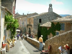 Ménerbes - Street in the village with houses and paintings exhibition