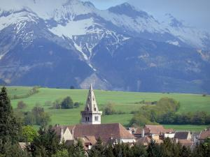 Mens - View of the Notre-Dame bell tower and rooftops of the village, trees, meadows and snow-capped Trièves mountains