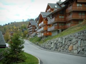 Méribel - Street of the ski resort (winter sports) with residences - chalets with wooden balconies