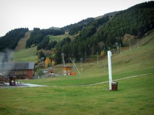 Méribel - Ski resort (winter sports) with ski lift (chairlift) of the ski area and spruces