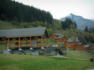 Méribel - Ski lift and residences - chalets of the ski resort (winter sports), trees in autumn, spruce forest and mountain with snowy summit