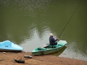 Mervent-Vouvant forest - Fisherman on a boat and the Mervent lake (Mervent dam)