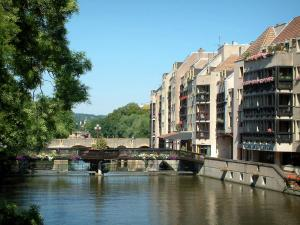 Metz - Moselle river, trees, bridges and buildings with woody balconies decorated with flowers
