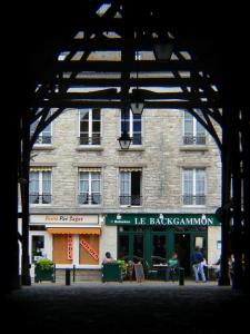 Milly-la-Forêt - Under the covered market hall, view of a café terrace and facade of a house in the village