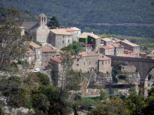 Minerve - Church and houses of the village standing on a rocky mountain spur, bridge and trees, in the Upper Languedoc Regional Nature Park