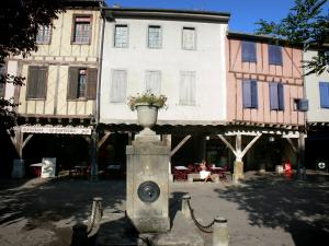 Mirepoix - Medieval bastide town: fountain and house facades on the central square (place des couverts)