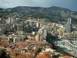 Monaco and Monte Carlo - City with its buildings, houses and swimming pool, mountain in background