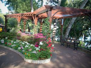 Monaco and Monte Carlo - Park decorated with flowers and pines with a bench