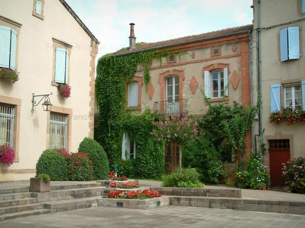 Monestiés - Main square in the village with its houses decorated with flowers and plants