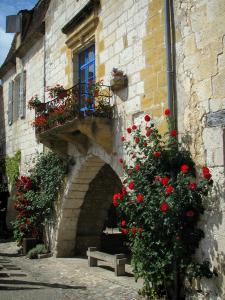 Monpazier - House of the place Cornières square (central square of the fortified town) with red climbing and a balcony decorated with flowers, in Périgord