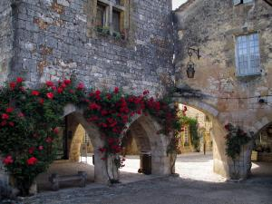 Monpazier - Houses with facades decorated with red climbing roses and arches of the Cornières square (central square of the fortified town), in Périgord