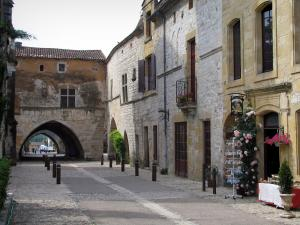 Monpazier - Street of the fortified town with its houses, and arches leading to the Cornières square (central square), in Périgord