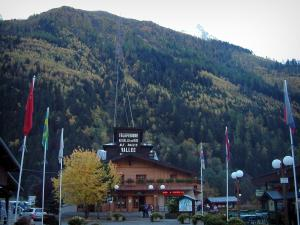 Mont-Blanc - In Chamonix: departure of the cable car to the aiguille du Midi, flags and forest in autumn