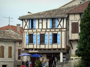 Montaigu-de-Quercy - Café Terrace facade and wood-framed house in the village