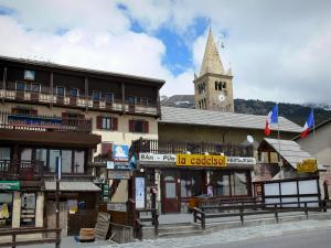 Montgenèvre - Ski resort (winter and summer sports resort): bell tower of the Saint-Maurice church with its headlight, chalet, French flags and shops