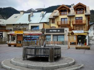 Montgenèvre - Ski resort (winter and summer sports resort): wooden fountain, shops and houses