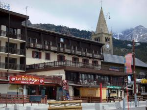 Montgenèvre - Ski resort (winter and summer sports resort): bell tower of Saint-Maurice church with its headlight, chalet and shops