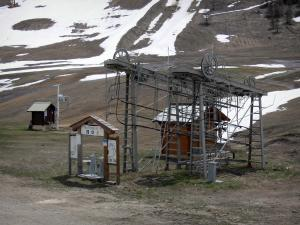 Montgenèvre - Winter and summer sports resort: ski lift and ski trail dotted with snow, in spring