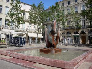 Montpellier - Fountain of the Marché-aux-Fleurs square, trees and buildings of the city