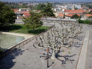 Montpellier - Peyrou district: square decorated with trees, lawns and lampposts with view of the roofs of the city