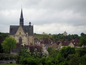 Montrésor - Collegiate church of Gothic style, houses of the village, trees and cloudy sky