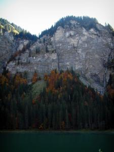 Montriond lake - Lake, spruces, trees in autumn, cliffs and waterfall in Haut-Chablais