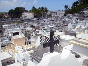 Morne-à-l'Eau cemetery - Black and white checkered tombs, with a view of the façades of houses in the town