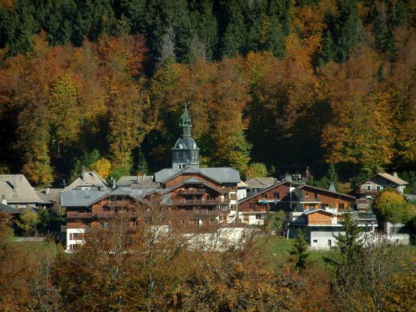 Morzine - Trees in autumn, church bell tower and chalets of the village (winter and summer sports resort), in Haut-Chablais