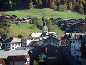 Morzine - Trees, alpine pastures, bell tower of the churchthe houses and chalets of the village (winter and summer sports resort), in Haut-Chablais