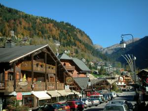 Morzine - Street of the village (winter and summer sports resort) with chalets, shops and view of the forest, in Haut-Chablais