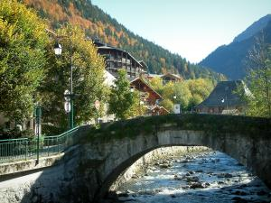Morzine - Bridge spanning the river, trees, lampposts and over of the village (winter and summer sports resort), forest in autumn, in Haut-Chablais