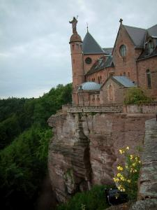 Mount Sainte-Odile - Convent (monastery) at the top of the pink sandstone cliff, wild flowers and trees in the forest below