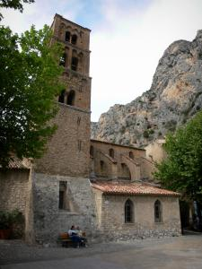 Moustiers-Sainte-Marie - Notre-Dame-de-l'Assomption church and its bell tower, trees and cliff