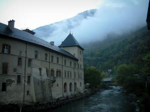 Moûtiers - Building by the River Isère, clouds and hill covered with trees