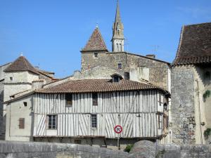 Nérac - Facades of old houses in the old Nérac medieval town and bell tower of the Notre-Dame church overlooking the place